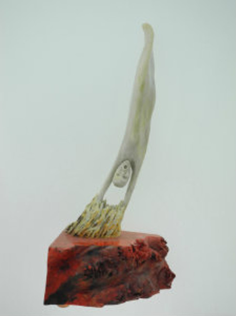 """""""Descending Soul"""".  Deer antler carving of a soul descending into hell. Mounthe on a piece of stabilized (with red dye) California buckeye burl wood. 6.5"""" X 3.25""""."""