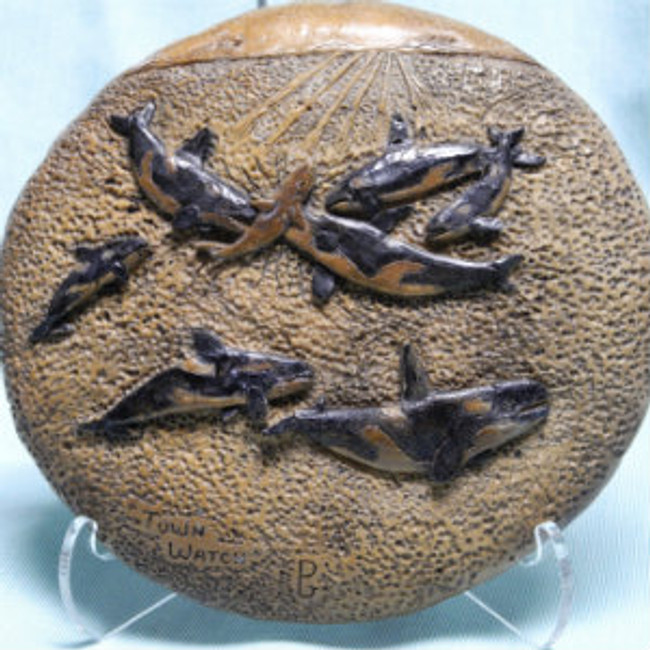 """Town Watch"". A pod of killer whales attacking an invading shark. Carved on a fossil whale intervertebral disc by Paul Grussenmeyer. 6.5"" diameter. Clear stand."