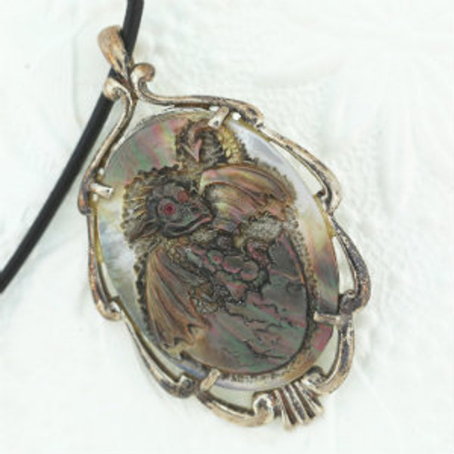 "Dragon Hatching carved on black mother-of-pearl by Paul Grussenmeyer, ruby eyes antiqued sterling silver pendent frame and clasp, greek leather cord. 16.5""."