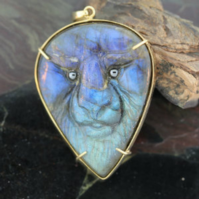 Carved labradorite African Lion face with hematite eyes mounted on a 14kt gold frame by Paul Grussenmeyer.