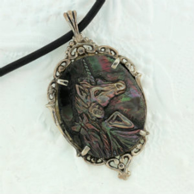 "A fairy with unicorn and butterfly carved on black pearl by Paul Grussenmeyer. Set in an antiqued sterling silver frame. 16.5"" Greek leather cord."
