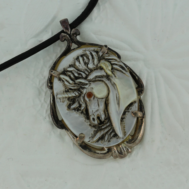 "Unicorn profile carved on mother-of-pearl with a ruby eye, mounted on an antiqued sterling silver frame by Paul Grussenmeyer. 16"" Greek leather cord."