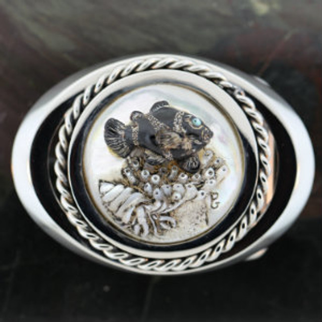 "Stainless steel belt buckle. Carved black coral clownfish and mother-of-pearl sea anemone and hermit crab. Opal eye. 2.7"" X 2""."