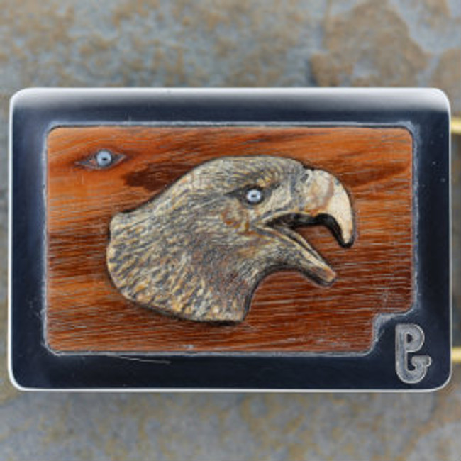 """The Double Eagle"". An eagle head carved from Picasso marble by Paul Grussenmeyer. Hematite eye in carving and on eagle emerging from the Tigerwood grain in the background. Mounted in Paul's signature series stainless steel belt buckle."