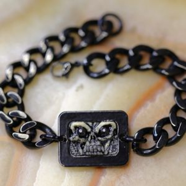 Paul Grussenmeyer carved American Moose antler skull face with hematite eyes mounted in a powder-coated aluminum frame on a Cuban Chain blackened stainless steel bracelet. Goes well with casual daily wear.