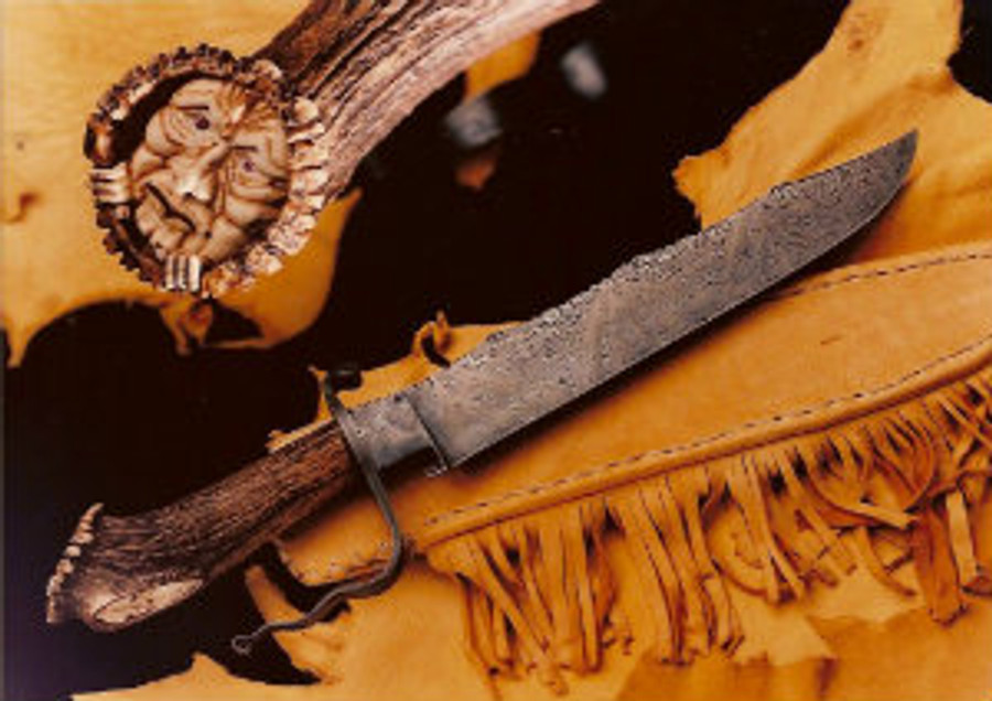 """""""Weeping Warlock"""". Carving of a forest being on the India Sambar crown stag handle on a Daniel Winkler forged damascus knife. 11"""" scalloped-back longknife blade wit full fileworked back, 17.5"""" overall length, curled damascus guard, African pink tourmaline eyes, emerald in the naval, sheath and display stand."""