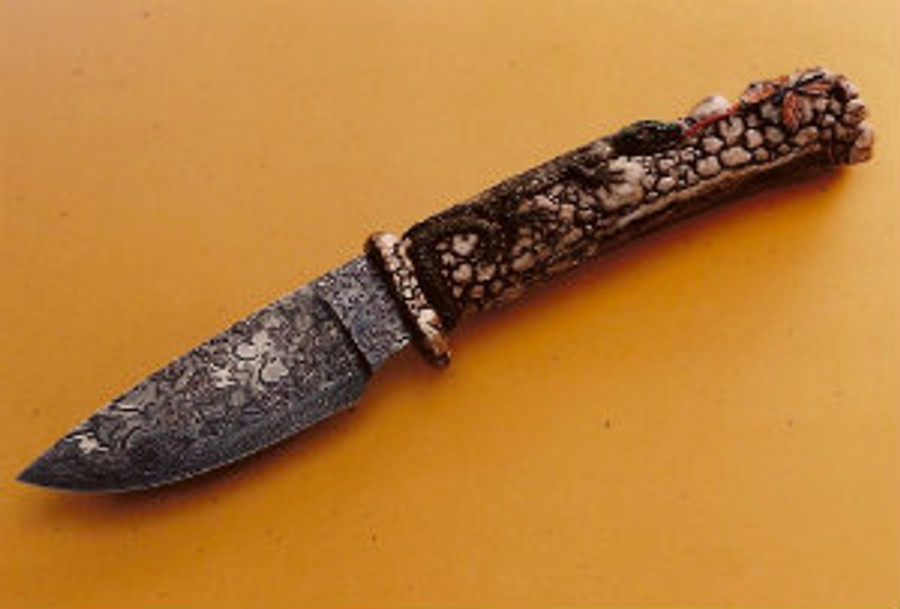 """Butterfly Hunter"". A fully carved India Sambar stag handle on a forged damascus knife by Master bladesmith, Hank Knickmeyer. This knife features aa lizard crawling over rocks with its tongue extended in pusuit of a butterfly meal. Ruby eyes, 4.13"" mosaic (butterflies, flowers, spiderwebs, and HK's) damascus blade, twist pattern edge, carved cast bronze guard, 9.38"" overall length. With a nice display stand."