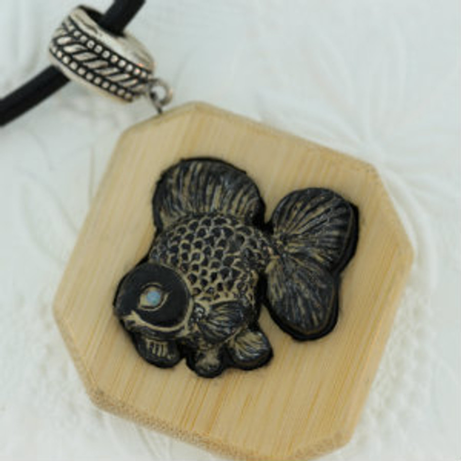 Japanese Ryukin Goldfish carved on Picasso black marble by Paul Grussenmeyer. Mounted on bamboo, opal eye, sterling silver bail and magnetic clasp.