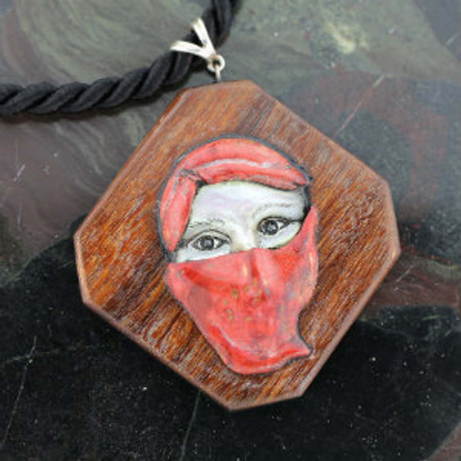 """Carved Pendent: """"Scheherazade"""", the legendary queen and storyteller of One Thousand and One Nights, with half veiled face carved from mother-of-pearl and red stabilized California Buckeye burl wood. With hematite eyes, mounted on Brazilian Ipe wood, sterling silver bail and clasp, twisted silk rope 18.25"""" necklace."""