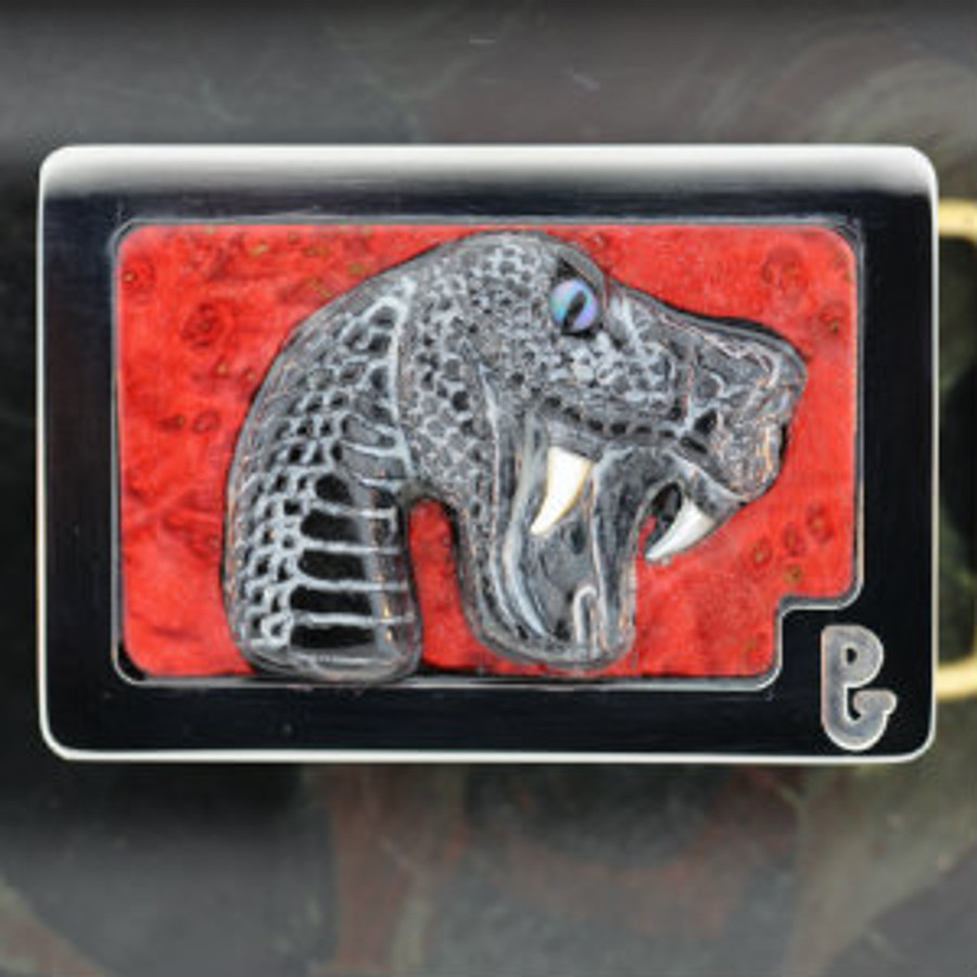 A viper snake carved on Picasso marble with opal painted pupil eye, pear fangs, and pearl glaze by Paul Grussenmeyer. Mounted on red dye stabilized California buckeye wood and Paul's signature series stainless steel belt buckle.