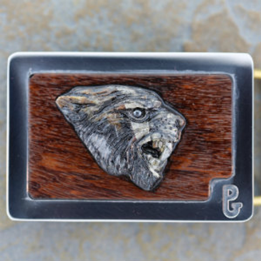 "Belt buckle with carved Picasso marble ""Sabertooth"" tiger and hematite eye set in Ipe wood by Paul Grussenmeyer. Mounted in Paul's signature series stainless steel belt buckle."