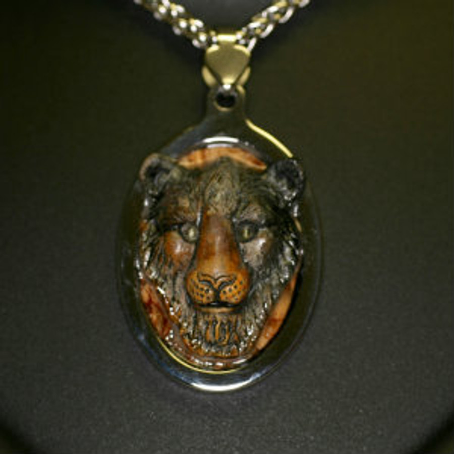 "Paul Grussenmeyer carved Picasso marble lion with exotic wood background, tiger eye stone eyes, mounted in stainless steel frame pendent and hung on 24"" stainless steel necklace with toggle clasp."