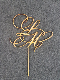Monogram MDF Cake Topper A personalised Monogram using the initials of a couple for their engagement, wedding, anniversary or even for a persons birthday. Simply decorate this MDF design however you like - paper, paint, glitter, embossing powder or leave it as is! Addition of Gold or Silver Glitter is an Additional $5 - purchase the additional glitter listing for this option. 150mm wide is the Standard Size Note: Wrap the sticks in foil or cling wrap before putting into the cake to avoid the MDF from going soggy. If you need this design smaller or larger to fit your cake size, let us know and we can resize it. We also produce custom designs - see the custom design listing for this option.