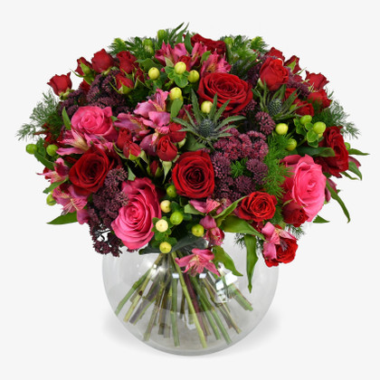 Crimson roses combine with velvety sedum to make a rich and moody colour palette.
