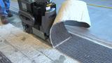 Walk-behind scraper removing carpet