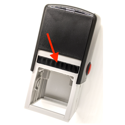 An arrow pointing to the ink pad that is built into a self-inking rubber stamp.