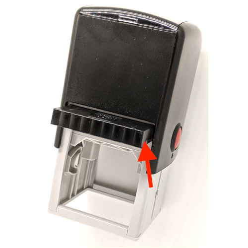 An arrow pointing to the ink pad showing how to push the pad back into the self-inking rubber stamp.