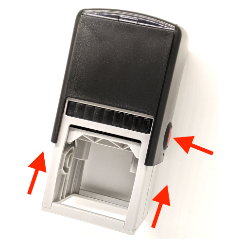 Arrows pointing up to show how to push the rubber stamp up and an arrow point to the red button showing the locking mechanism on the stamp.