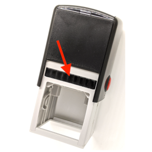 A self-inking rubber stamp with an arrow pointing to the built-in ink pad
