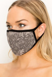 Left side/partial front view of Women's Lace Knit Floral Face Mask - Made in the USA with a gorgeous black lace design overlaying a beige fabric base.