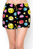 Front view of Buttery Soft Ladybugs and Hearts Dolphin Shorts with a red, yellow, pink, and blue ladybug design with pink hearts that contrasts a black background.