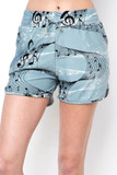 Front view of Buttery Soft Swirling Music Notes Dolphin Shorts featuring a soft blue fabric base decorated with a swirl of black and white music notes.