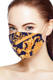 45 degree view of Chic Regal Royal Face Mask - Made in USA featuring an ornate gold filagree design on a navy background.