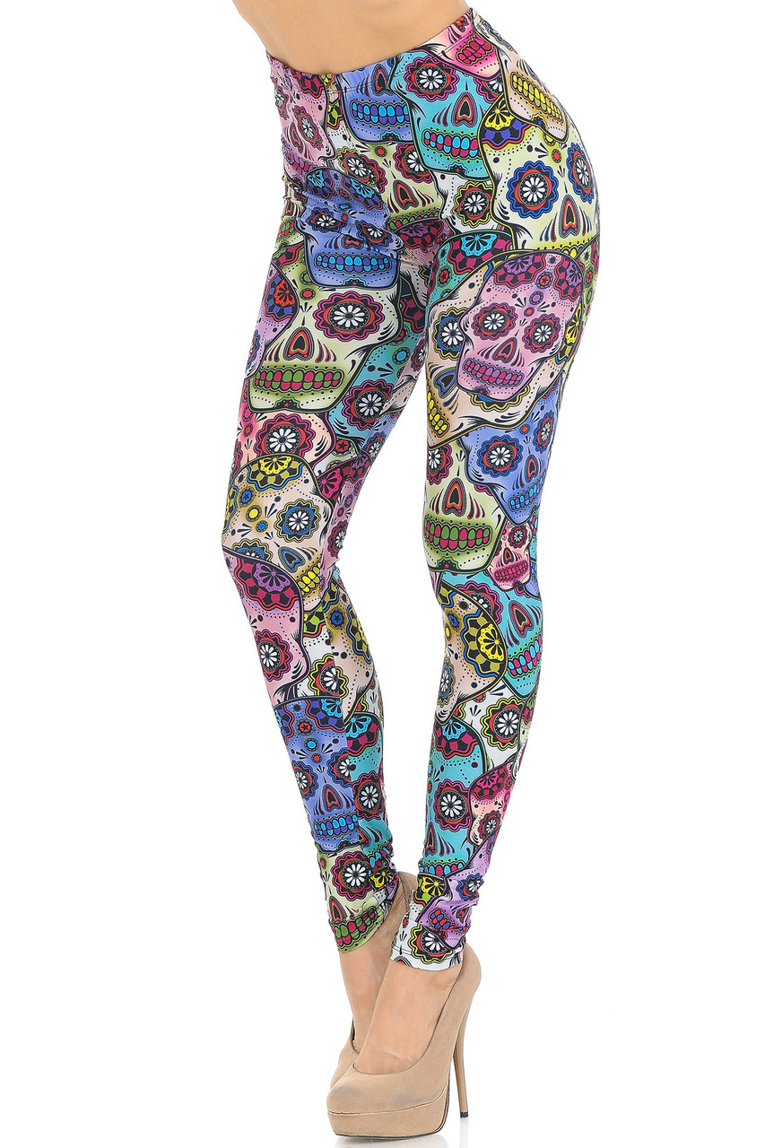 Angled front view image of Creamy Soft Sugar Skull Leggings with a colorful all over day of the dead themed skeleton head print with floral accents.
