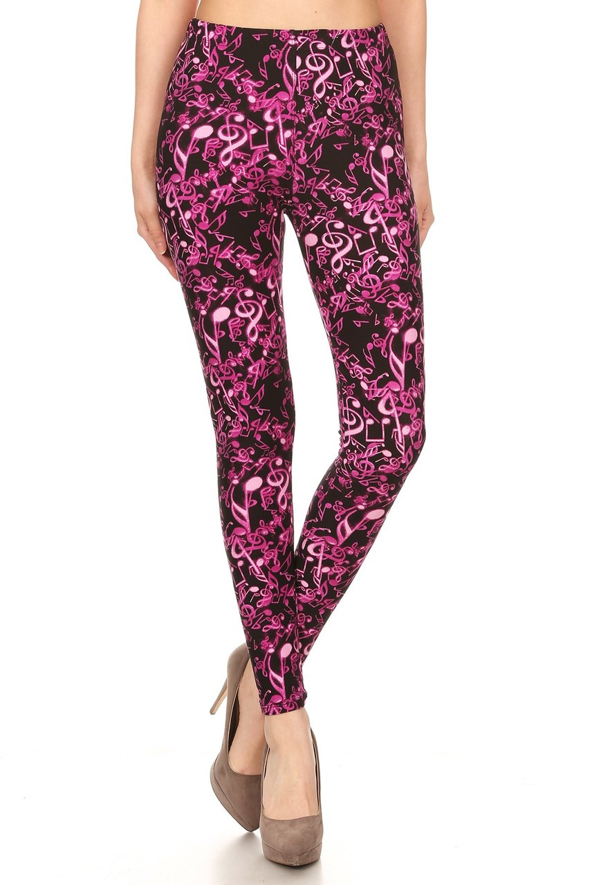 Crossed foot front view image of our Buttery Soft Electric Fuchsia Music Note Leggings with a mid ride elastic waist.
