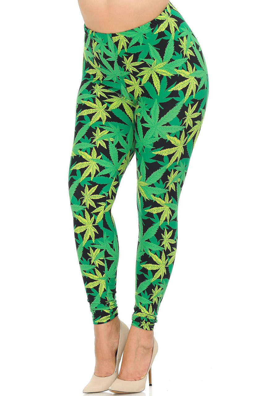 Angled front view image of our Buttery Soft Cannabis Marijuana Plus Size Leggings with a mixed green colored weed leaf print with a high contrast black background peeking through.