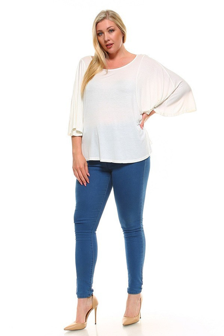 Full body image of Ivory Round Neckline 3/4 Flutter Sleeve Relaxed Fit Rayon Plus Size Top shown styled with medium wash denim skinny jeans and nude pumps.