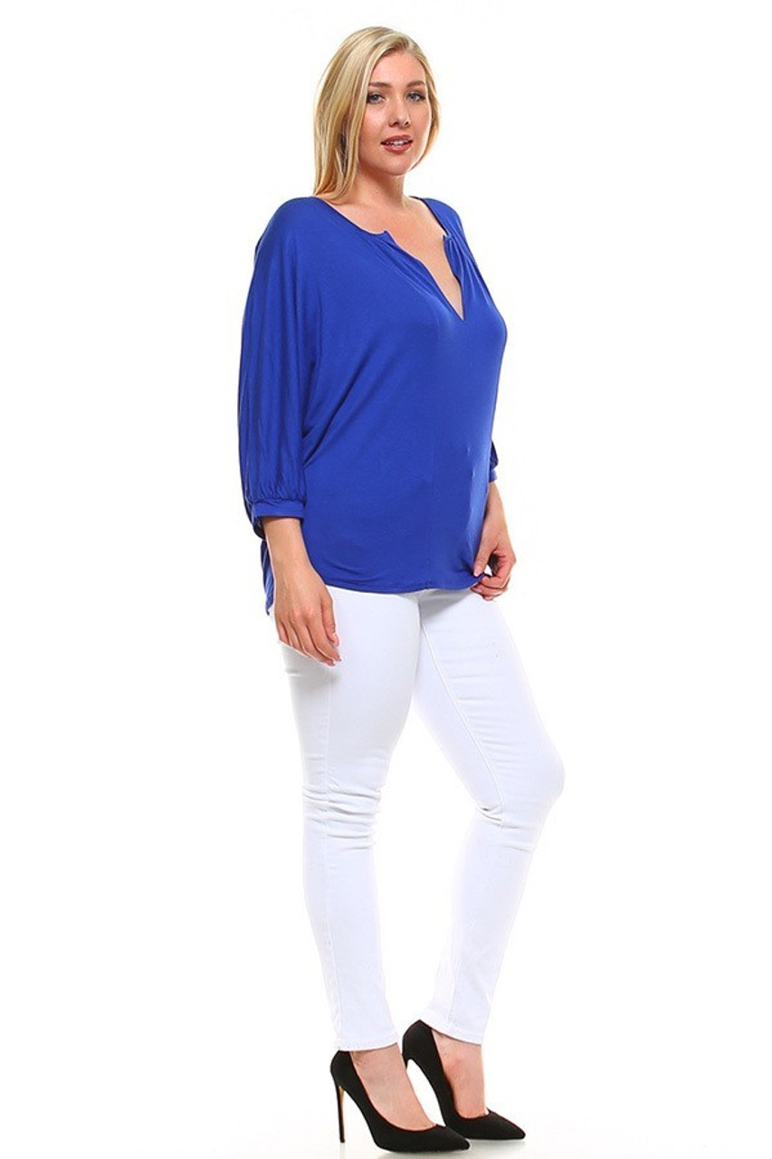 Full body view partial front/right side image view of Blue Split Round Neckline Relaxed Fit Dolman Sleeve Rayon Plus Size Top shown styled with white skinny leg pants and black pumps.