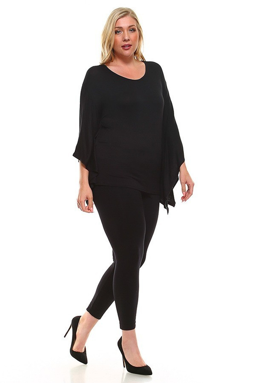 Full body image of  Black Round Neck Cape Style Sleeveless Rayon Plus Size Top shows styled with solid black leggings and black pumps.