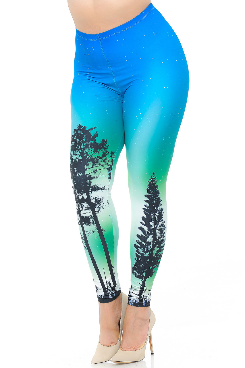 Angled front view image of our gorgeous Creamy Soft Blue Sunset Plus Size Leggings - USA Fashion™ featuring a colorful blue and green ombre star-filled night sky design with tree silhouettes.