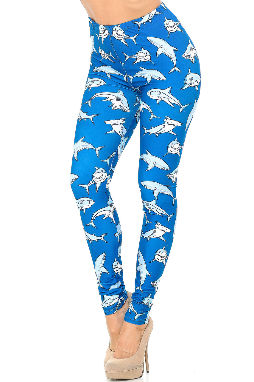 Angled front view image of Creamy Soft Shark Plus Size Leggings - USA Fashion™ with an all over mixed shark print on a bright blue background.