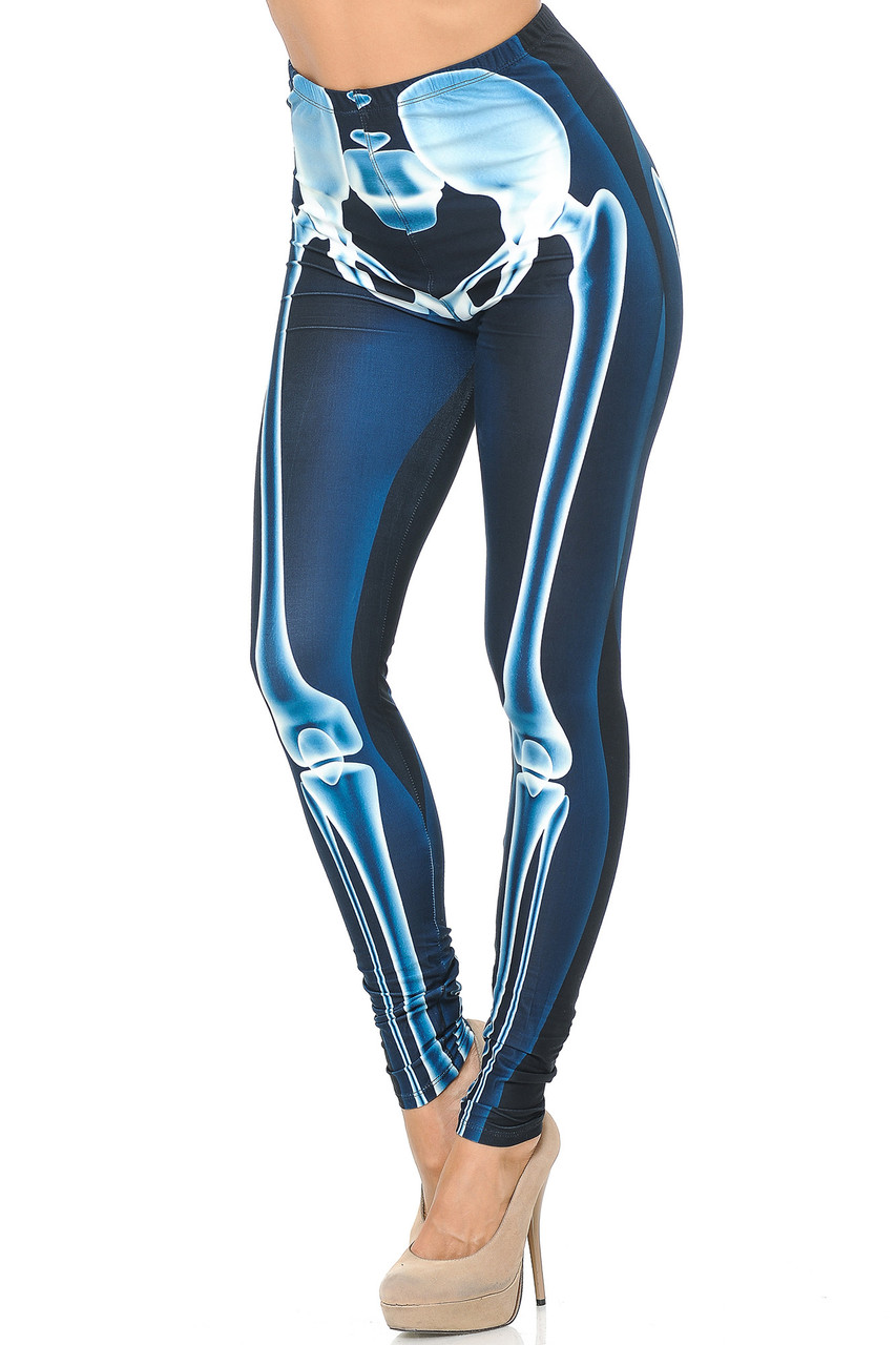 Angled front view image of Creamy Soft Radioactive Skeleton Bones Extra Plus Size Leggings featuring a glowing anatomical bone  scan of a lower body half in a blue color scheme.