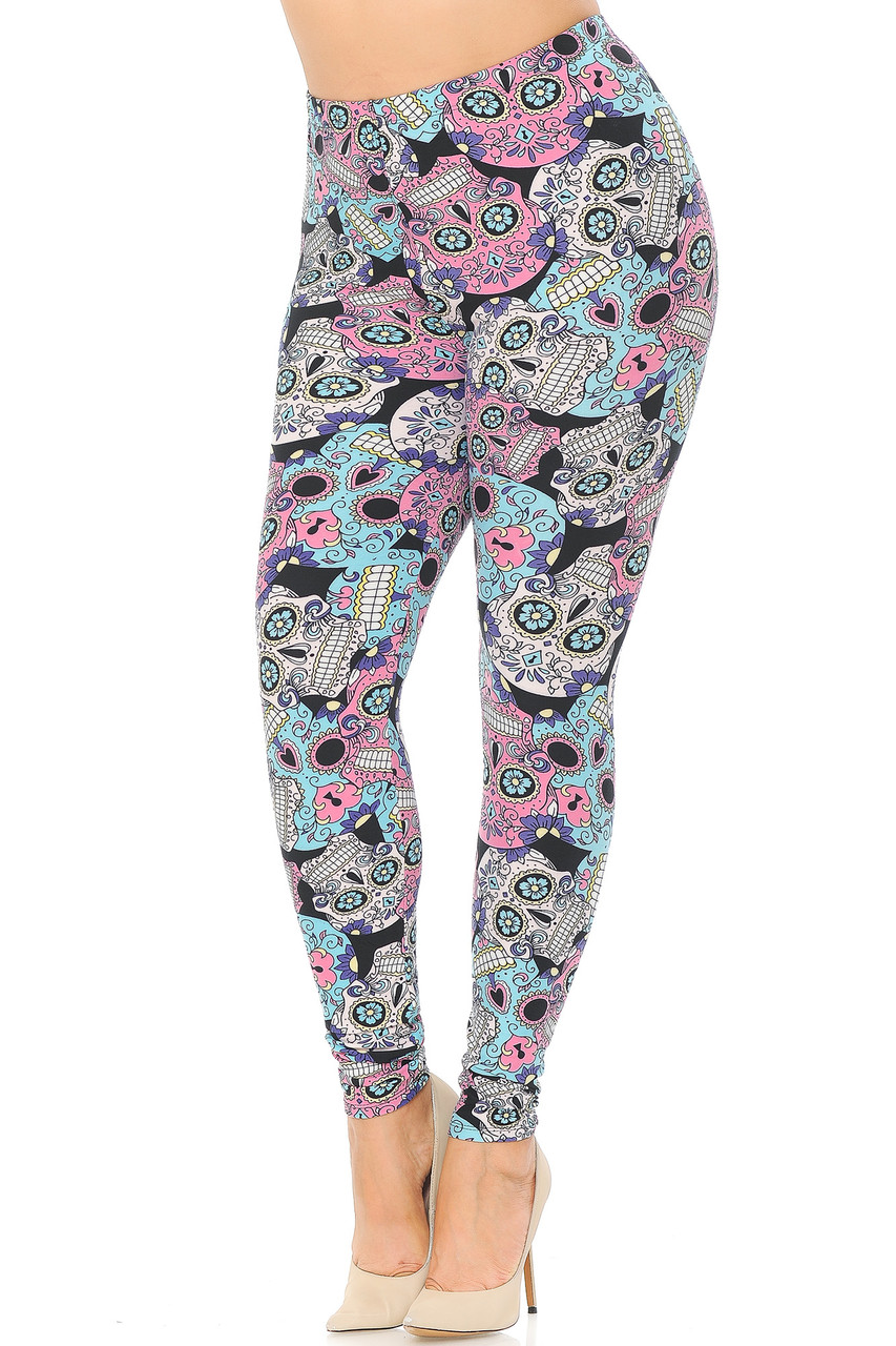 Angled front view image of Buttery Soft Pastel Sugar Skull Plus Size Leggings featuring a colorful soft toned pink blue and white all over intricately decorated sugar skull design with floral touches against a black background that peeks through a little.