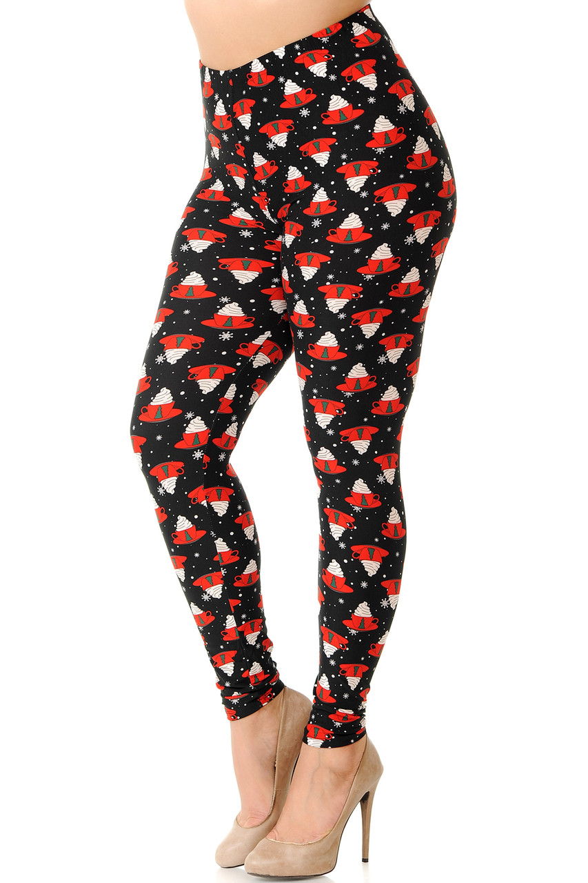 Left side right bent knee view of our heartwarming Buttery Soft Mocha Cappuccino Christmas Coffee Plus Size Leggings featuring red mugs decorated with Christmas trees, and topped with whipped cream against a black background.