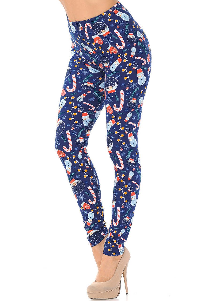 Left side right bent knee image of Buttery Soft Memories of Christmas Plus Size Leggings featuring a print that includes snowmen, mitten, snow globes, and christmas lights on a blue background.
