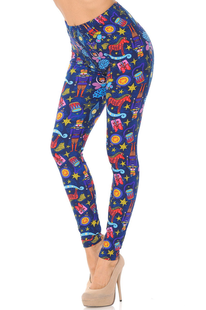 Left side right bend knee view of Buttery Soft Nutcracker Christmas Trinkets Leggings featuring a festive colorful print of iconic imagery from the tale of the Nutcracker.