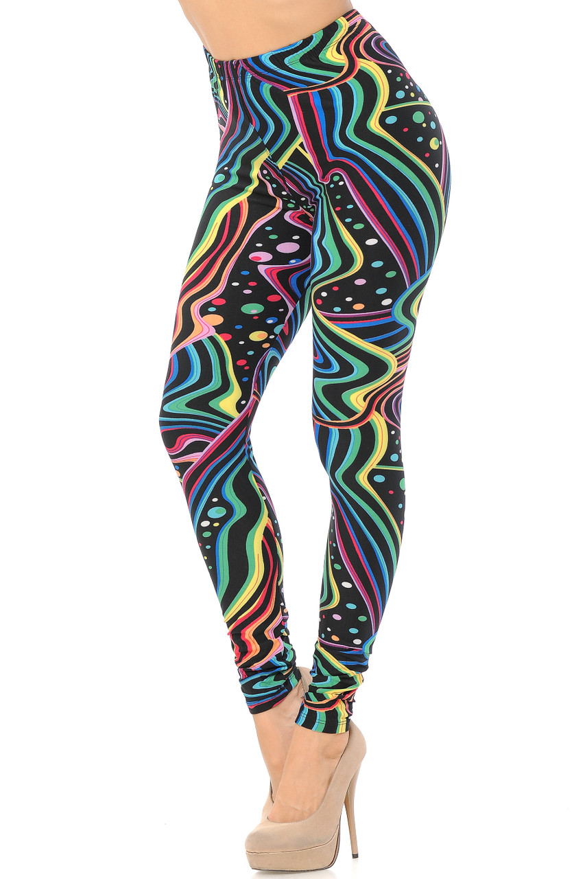 Our vibrant, fun, and sassy Buttery Soft Rainbow Bash Leggings feature an eye-catching multi-colored wavy and polka dotted design that contrasts a black background.