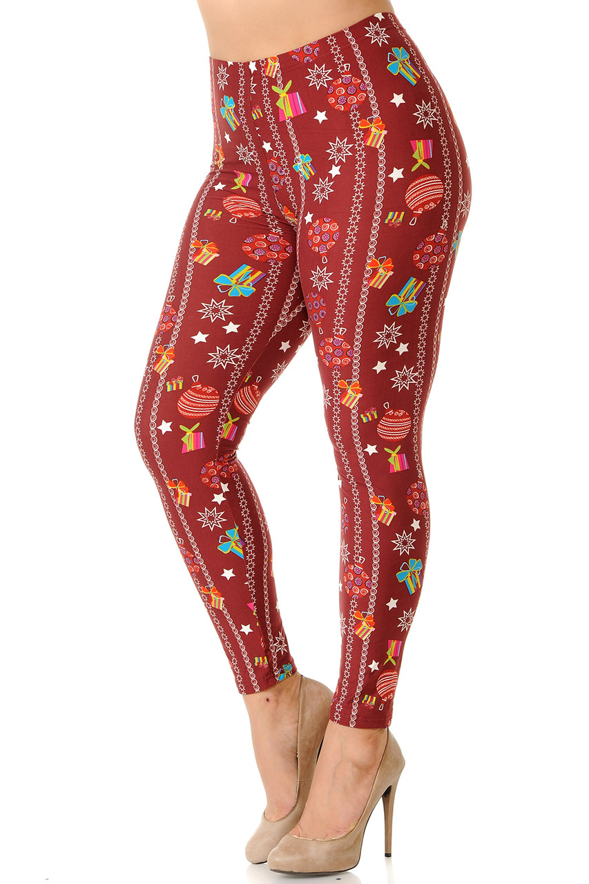 Left side view image of Buttery Soft Burgundy Christmas Ornaments Plus Size Leggings featuring a deep red background designed with vertical  decorative stripes, presents, ornaments,, and stars.