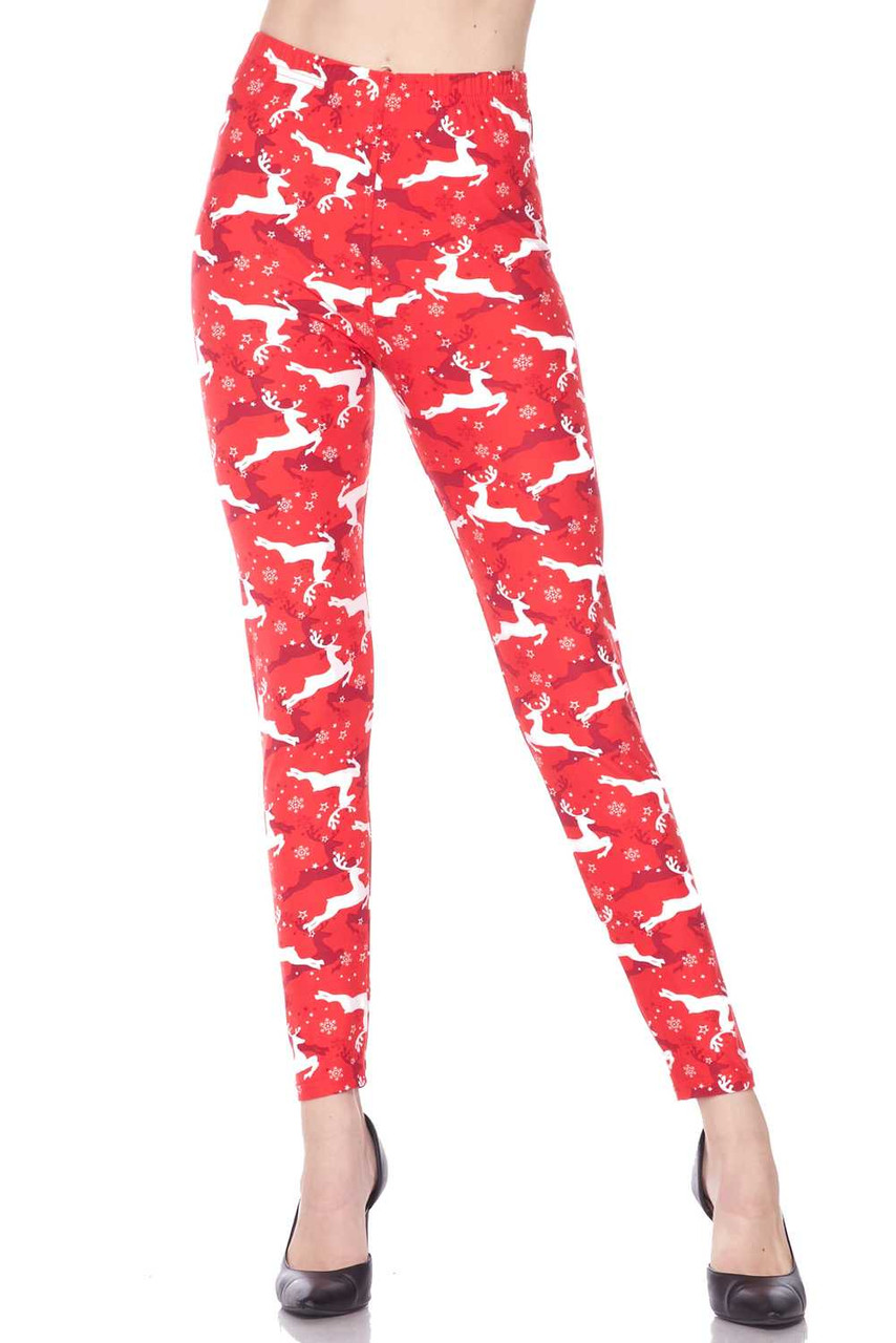 Front view image of our vibrant  Buttery Soft Ruby Red Leaping Reindeer Christmas Leggings with a festive all over white and burgundy on red reindeer print.