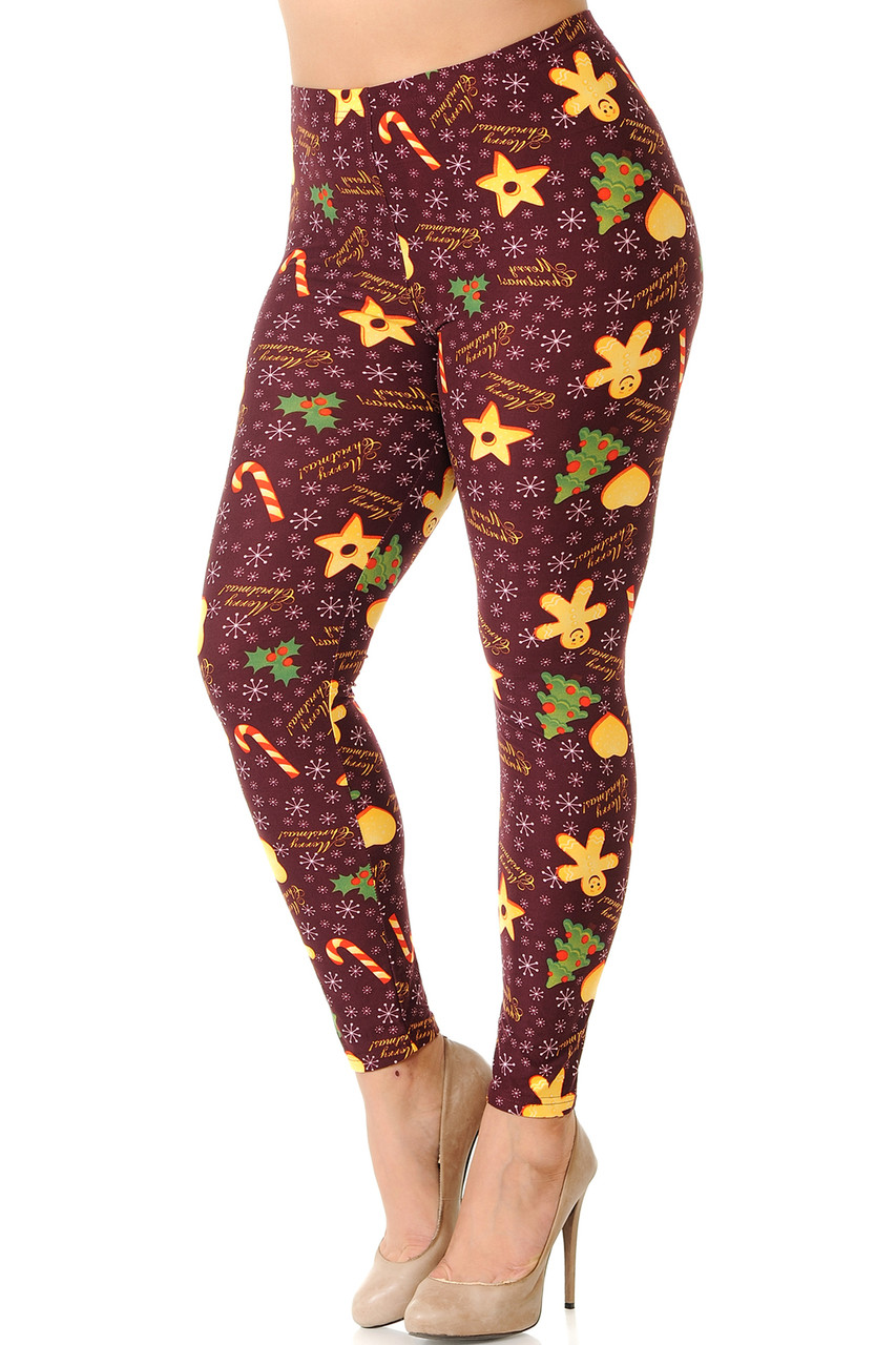 """Partial front/left image view of Buttery Soft Merry Christmas Treats and Cookies Plus Size Leggings featuring a burgundy background decorated with snowflakes, holiday cookies, and the words """"Merry Christmas."""""""