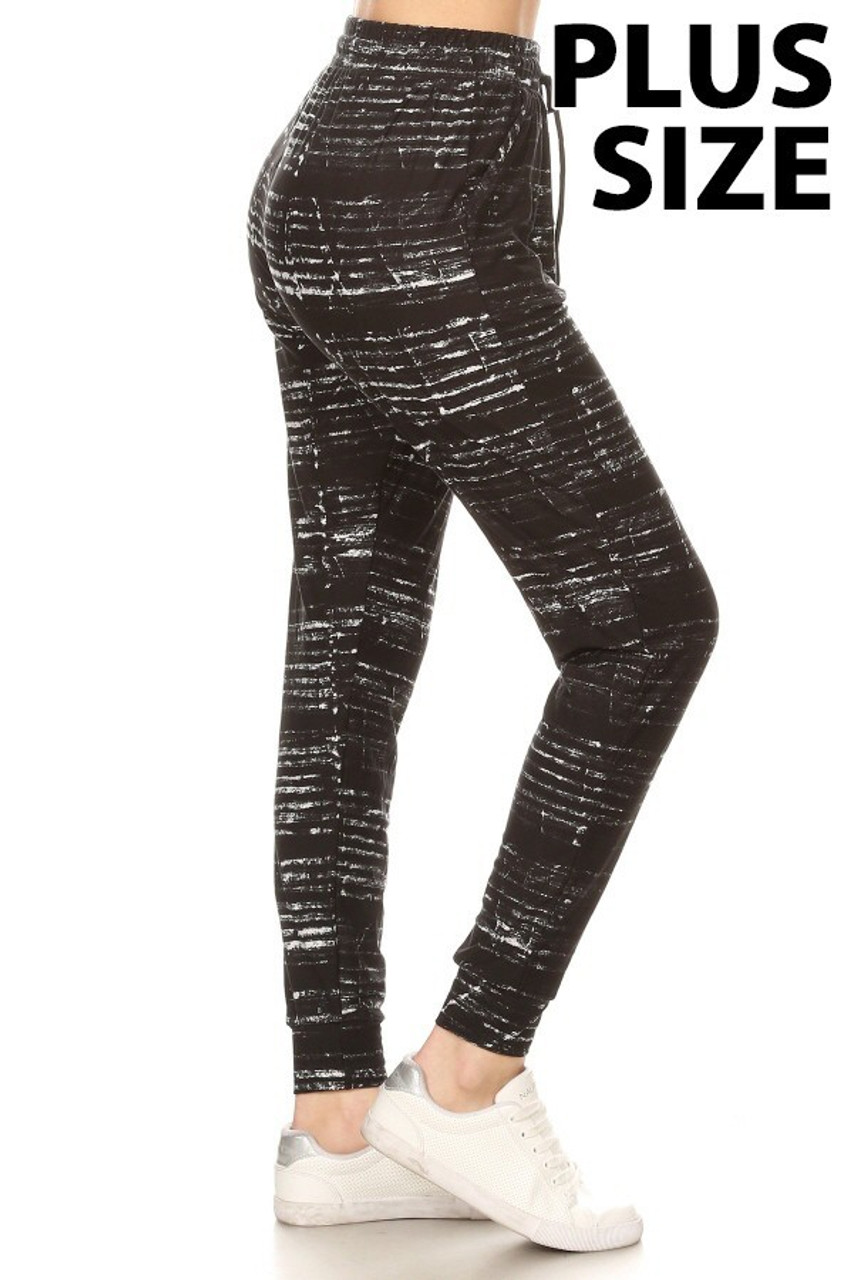 Right side view of Buttery Soft Ebony Moondust Plus Size Joggers showcasing a distressed white horizontal striped look that contrast a black fabric base, and pairs with a top of any color for any season.
