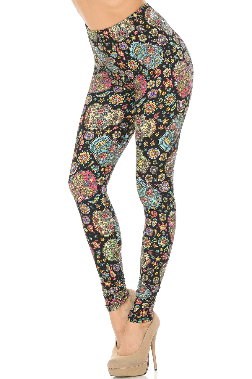 Front view image of Buttery Soft Mandala Sugar Skull Leggings with a super ornate skeleton head design in a multicolored palette atop a white background with floral accents.
