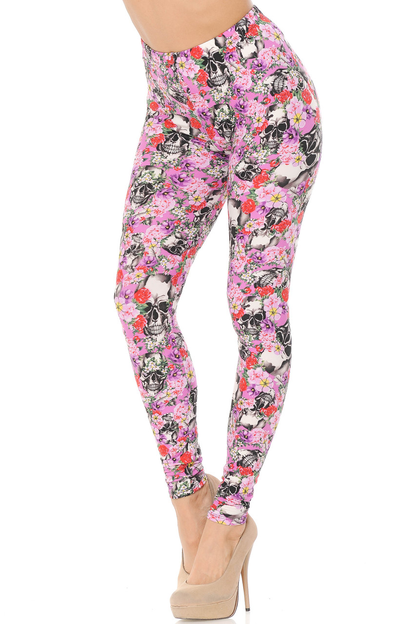 Partial front view image of our Buttery Soft Pink Blossom Skulls Leggings featuring an all over pink and red hued rose design mixed with edgy skulls against a pink background.