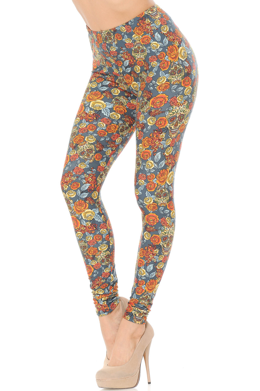 Partial front view image of Buttery Soft Charcoal Rose and Skulls Leggings featuring a feature an all over orange and yellow Autumn inspired floral color scheme mixed with sugar skulls against a charcoal background.