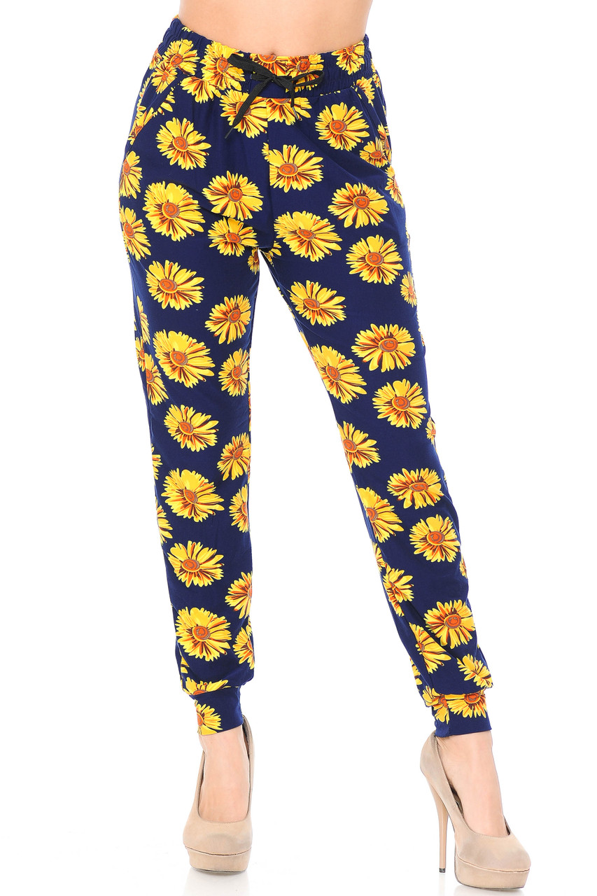 Front view image of our Buttery Soft Summer Daisy Joggers with a yellow flower print on a navy blue background.