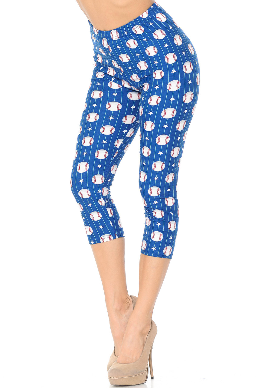 These Buttery Soft Boys of Summer Baseball Capris feature a vibrant blue background, and are decorated with an all over print of baseballs, white stars, and white stripes.